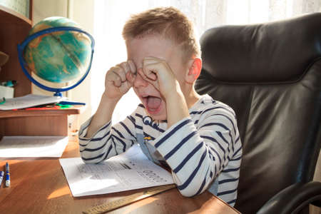 school-age boy crying and screaming while doing homework. the concept of heavy pressure education