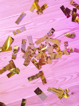 golden confetti on pink colored wooden floor or table background