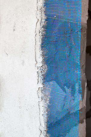 wall with applied plaster and blue reinforcing grid sticking out from under it Stock Photo