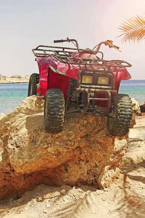 Quad bike ATVs on rock on beach of sea