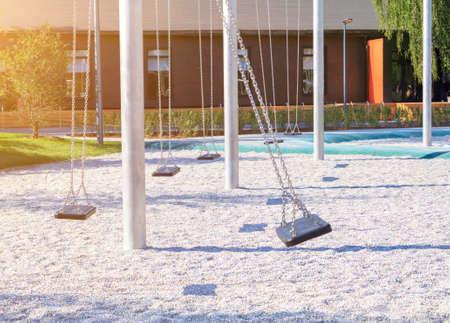 empty lonely swings with sun light in modern park