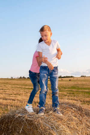 happy children jostling on haystack at sunset. kids, girl with boy standing in field