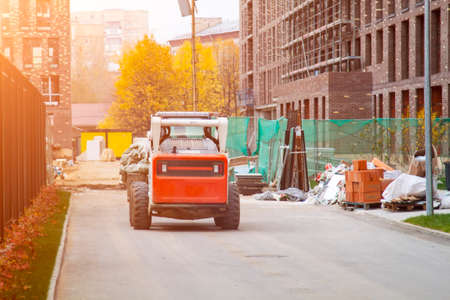Skid loader drives through yard of new high rise building with garbage bags in bucket
