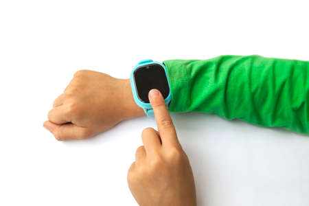 boy looks at information on digital clock pressing screen with his index finger. Modern childrens technologies. GPS tracker for kids, child tracking and parental control concept.