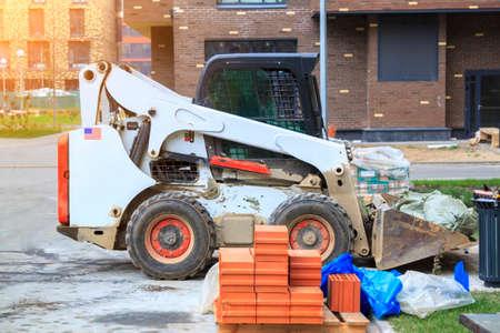 Skid loader is in yard of new multi storey building with garbage bags in bucket Stock fotó
