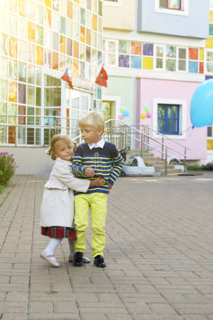 Adorable little girl in coat hugs boy with blue ball on territory of kindergarten on sunny day