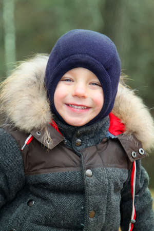 happy smiling boy in warm clothes and hat covering his neck from cold wind llooking at camera in autumn outdoor