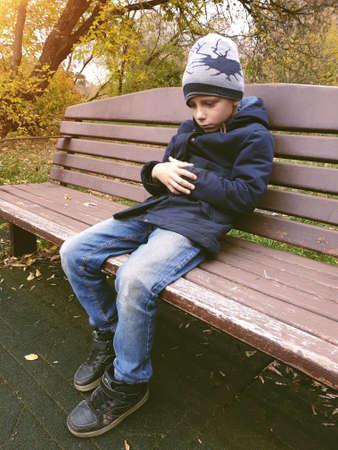 sad boy sitting on bench alone outdoor