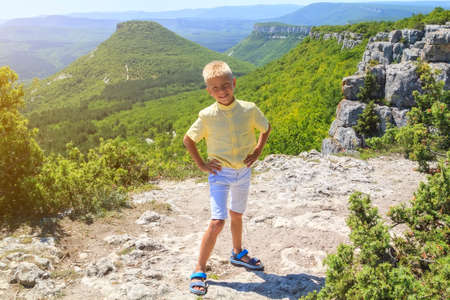 fearless adorable little happy boy stand on steep edge of limestone plateau overlooking the valley