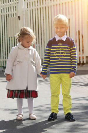 Adorable little girl in coat holds boy hand near kindergarten on sunny day. Childhood friendship