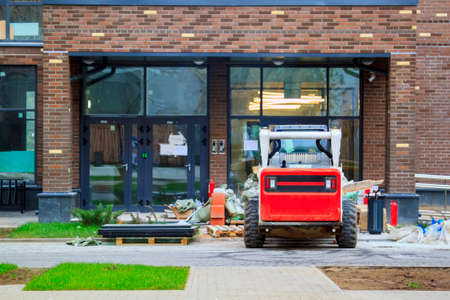 Skid loader stands in front of entrance to new multi-storey house and waits for garbage to be loaded into bucket. Mini bulldozer waiting for cargo in front of porch Stock fotó