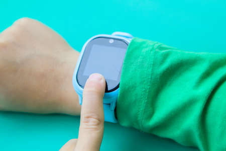 boy wants to call his parents on digital clock touching screen with his index finger. Modern children technologies. GPS tracker for kids, child tracking and parental control concept.
