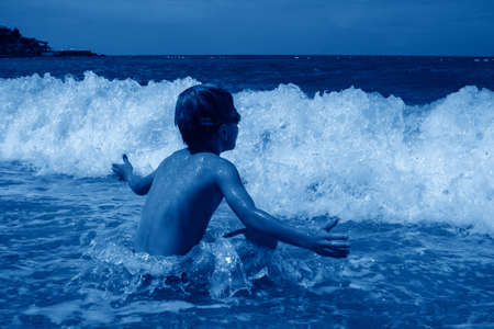 little boy in swimming goggles sitting on pebble on beach and enjoys surging waves with white foam