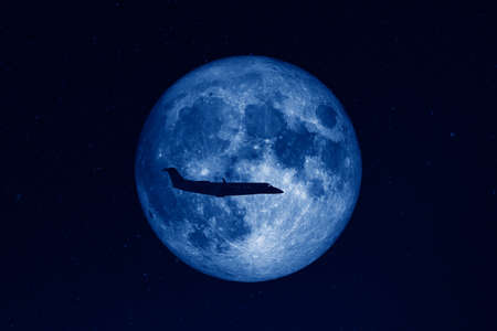 Silhouette of private jet plane flying against background of huge full moon in dark starry space. Stock Photo