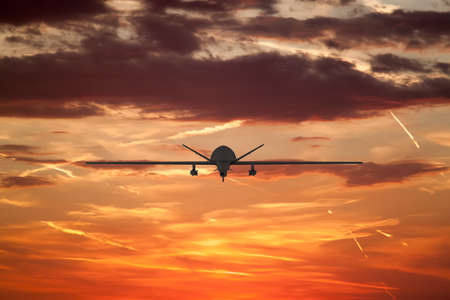 military UAV airplane flies against backdrop of beautiful view of the sunset sky orange with clouds and condensation traces Reklamní fotografie