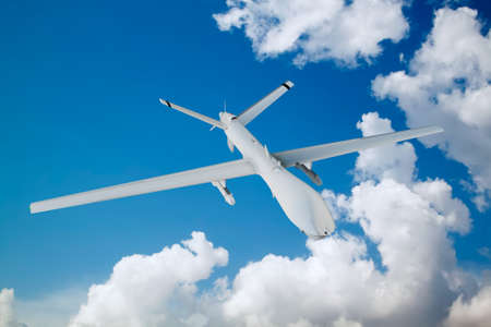 military UAV airplane flies against backdrop of beautiful clouds on blue sky background Stock Photo