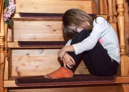 sad little girl is sitting on the stairs with her knees clasped and her long hair hanging down