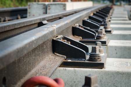 welded: Steel clips, rail,Section of welded railway track showing the weld, fastenings, sleepers and ballast.