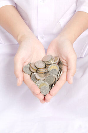 frugality: Hand coins to stack of coins on white background background frugality accumulated savings.