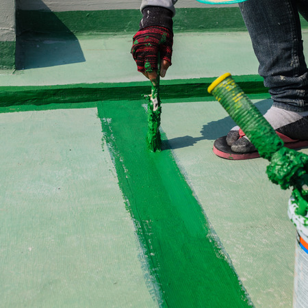 waterproofing: painting the roller brush, for waterproofing. Stock Photo