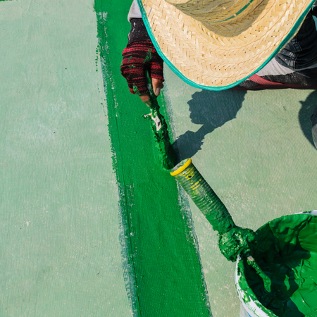 ruberoid: painting the roller brush, for waterproofing. Stock Photo