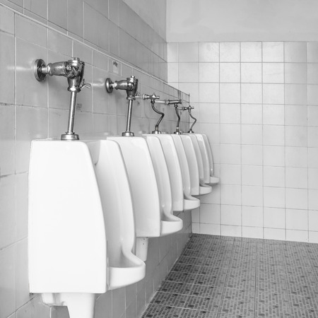 Closeup white urinals in men's bathroom, design of white ceramic urinals for men in toilet room