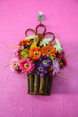 Spring flowering pansies bright and cheerful in a wicker hanging basket on a red brick wall