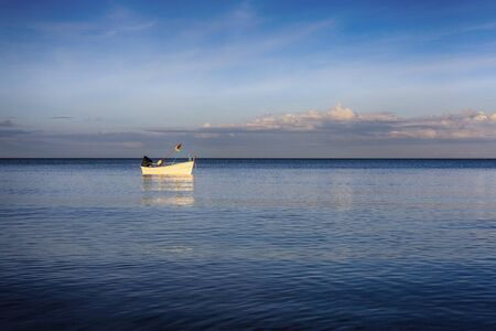 White fishing boat floats in the evening sea.