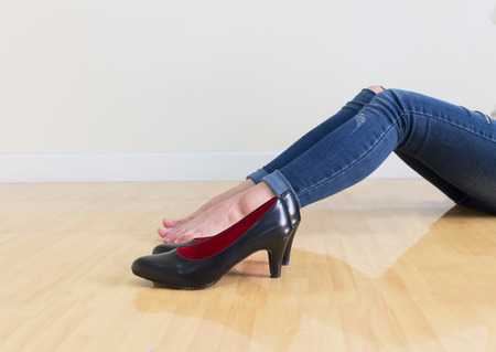 Young office Woman blue jeans Wearing High-heeled shoes ,sitting cross-legged On a white background Stock Photo