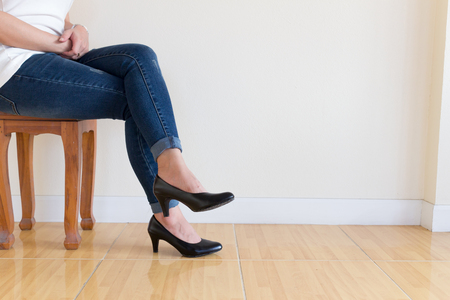 Woman blue jeans Wearing High-heeled shoes ,sitting cross-legged On a white background Imagens