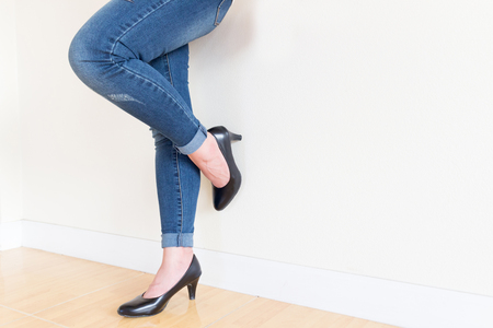 Woman blue jeans Wearing High-heeled shoes ,sitting cross-legged On a white background Stock Photo