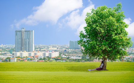 Lady Under the tree Grassy sky of Earth day Ecology concept Stock Photo