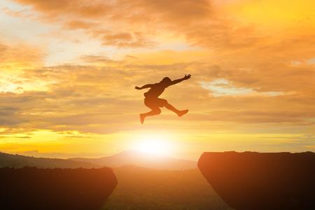 Hommes sauter la lumière du soleil falaise sur la silhouette Banque d'images