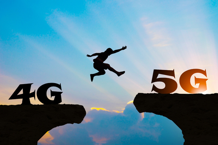 Technology 4G go to 5G Men jump over silhouette 免版税图像