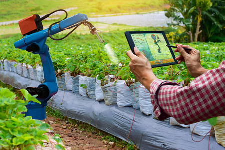 Farmer holding a tablet smart arm robot work agricultural machinery technology