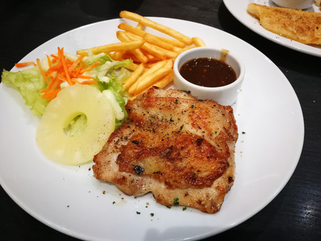 Chicken steak in a white plate on a black table
