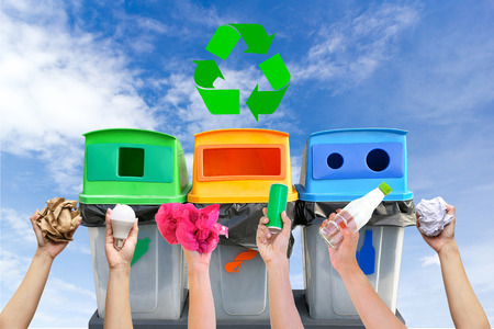 Hand holding garbage recycling bins on sky background