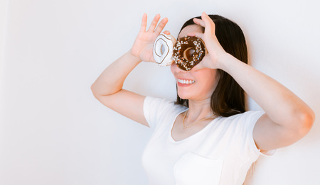 Women asia wearing white shirts holding donuts to eat