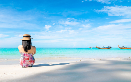 Women sitting back on the beach and sea have a holiday summer relaxing and travel bright sky koh lipe thailand Banco de Imagens - 124531720