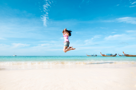 Happy jumping women the beach and sea have a holiday summer relaxing and travel bright sky koh lipe thailand