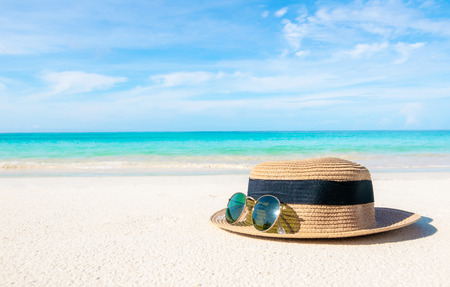 Hats and glasses placed on the beach and sea have a holiday summer relaxing and travel bright sky koh lipe thailand Banco de Imagens - 124532470
