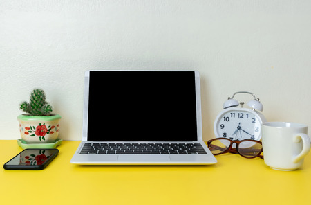 Laptop placed on a yellow table background of business working place with cup coffee, Empty workspace Banco de Imagens - 124532477