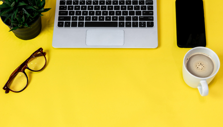 Laptop placed on a yellow table background of business working place with cup coffee, Empty workspace Banco de Imagens - 124532484