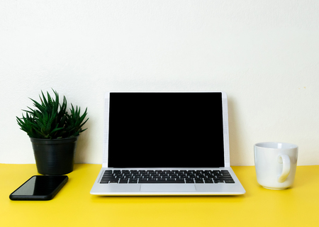 Laptop placed on a yellow table background of business working place with cup coffee, Empty workspace