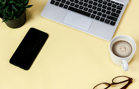 Laptop placed on a yellow table background of business working place with cup coffee, Empty workspace Banco de Imagens - 124532532