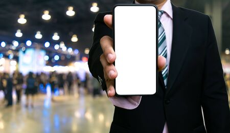Businessman using holding smartphones white screen showing information on bokeh background and people blurred