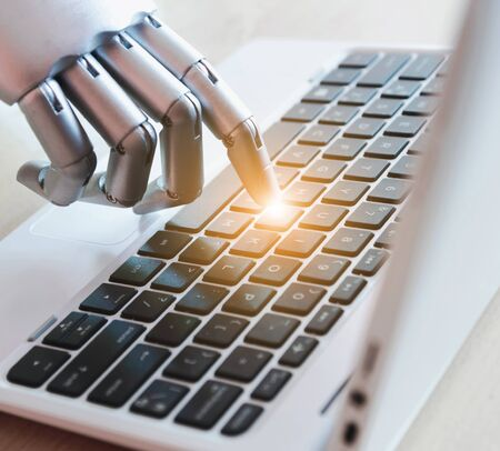 Robot hands and fingers point to laptop button advisor chatbot robotic artificial intelligence concept with light effect