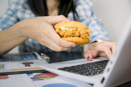 Women work and eat hamburgers to eat lunch in office