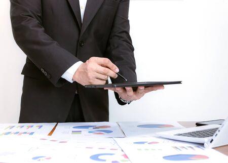 Businessmen holding tablets, analyzing graphs on desks, white background. Stock fotó