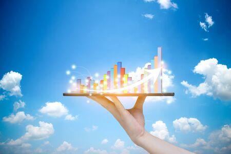 Tablet auf Hand Wachstumsfortschrittsdiagrammanalyse oder Erfolgsgeschäftskonzept Himmelshintergrund